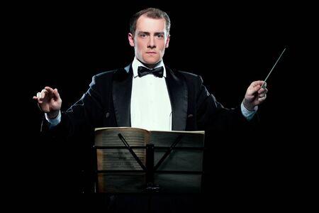 Studiofoto van muziekdirigent die zijn stokje vasthoudt