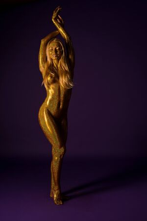 Nude blonde covered with gold glitter view Stock Photo