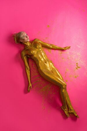 Woman covered with gold glitter high angle view