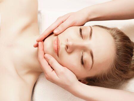 Spa. Mujer disfrutando de un masaje facial anti-envejecimiento