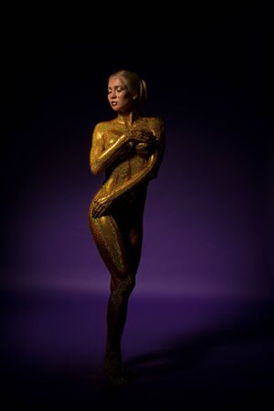 Naked blonde covered with gold glitter view Stock Photo