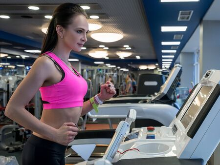 Shot of focused girl running on treadmill in gym