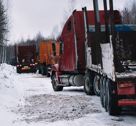 Empty long vehicles on winter road among forest