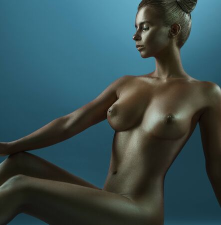 Woman art nude portrait with gold skin