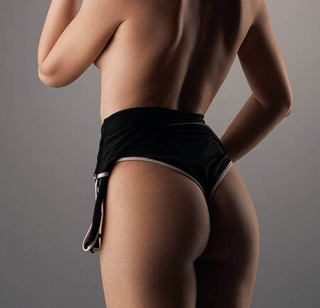 Sexy blonde posing topless with her back to viewer