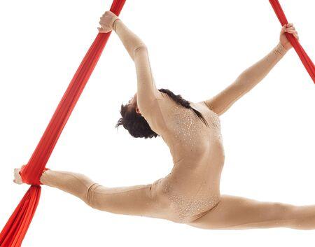 Young girl doing splits on aerial silks in studio