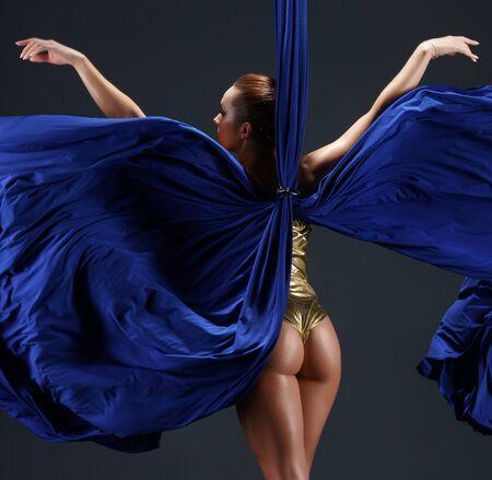 Slim girl in gold bodysuit on blue aerial silks
