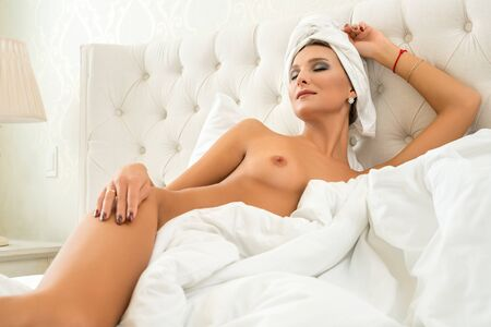 Gorgeous nude girl relaxing in bed view