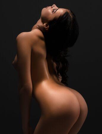 Nude sexy dancer posing at dark studio, rear view