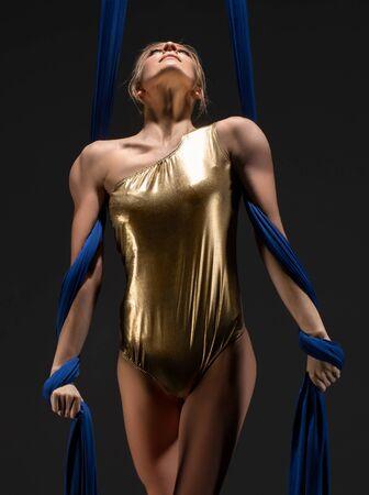 Sexy girl in gold lingerie on aerial silks Zdjęcie Seryjne