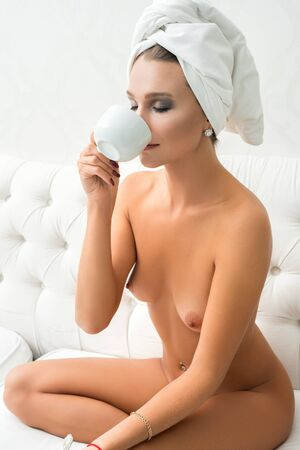 Gorgeous nude girl having tea in bed view