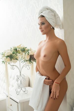 Gorgeous nude girl in luxurious hotel room Standard-Bild