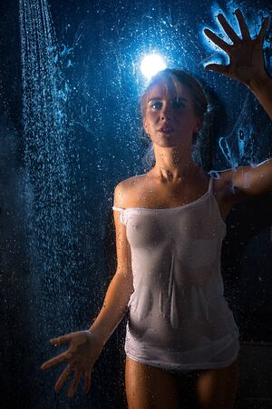 Woman in wet t-shirt in shower view in the dark