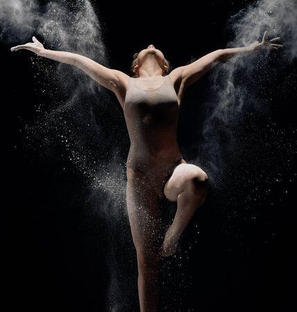 Slender girl dancing in white powder cloud