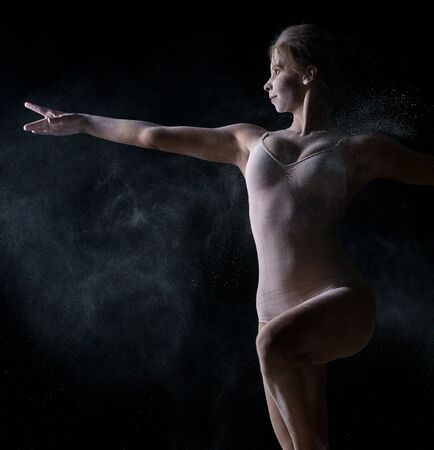 Dancer jumping gracefully in cloud of powder