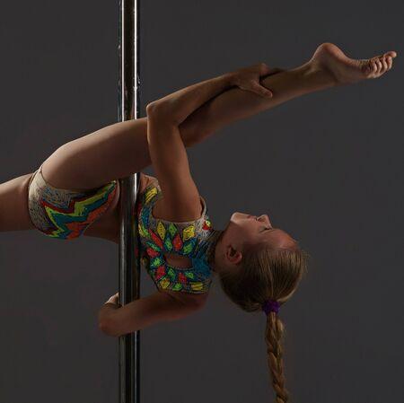 Adorable petite fille exerçant sur pylône en studio