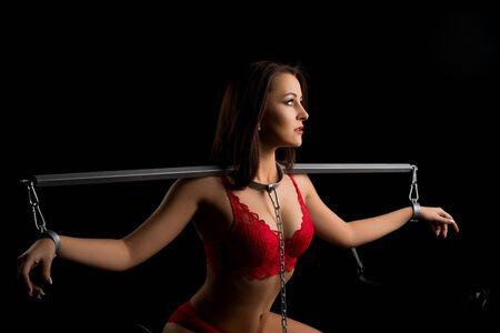 Femme fixée avec des chaînes en métal vue dans le noir Banque d'images