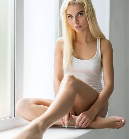 Nice blonde sitting on window sill in studio