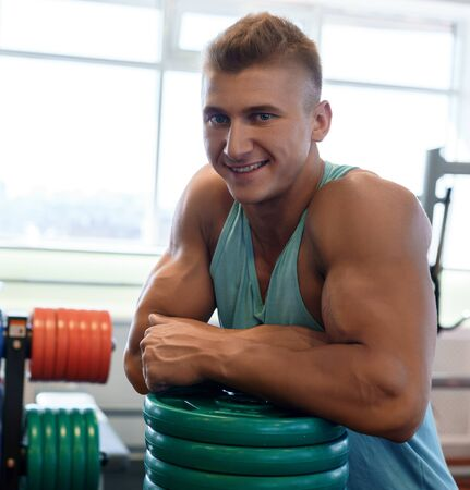 Young handsome bodybuilder posing in a gym
