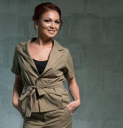 Beautiful woman in khaki pantsuit studio shot