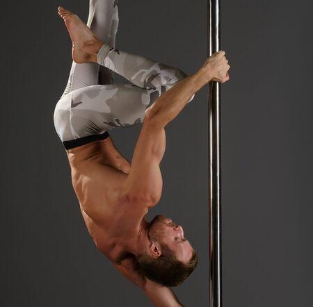 Male dancer at pylon in pole dance studio