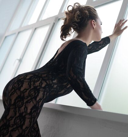 Sexy girl in lace lingerie looking out the window