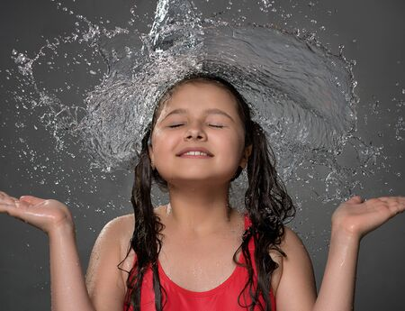 Young girl catching water stream from top