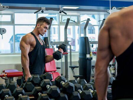L'homme regarde dans le miroir pendant les exercices avec des haltères