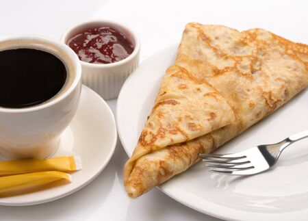 Dessert meal - shot of fresh sweet crepe with berry sauce and cup of strong coffee on white background