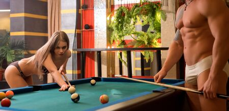 Young sexy lovers playing billiards in sauna