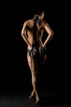 Slim nude woman in gray paint cropped rearview