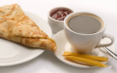 Pancake served with full cup of coffee and jam