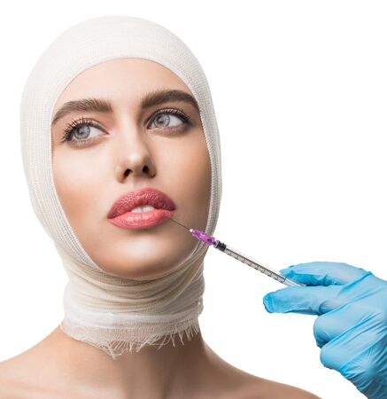 Girl her head bandaged getting beauty injections Foto de archivo