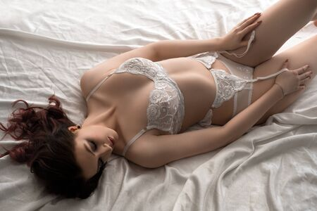 Young brunette in white lingerie high angle view