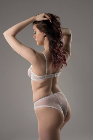 Young woman in white lace lingerie rearview