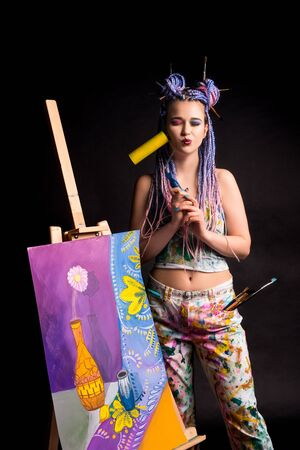 Stylish artist near easel with painting