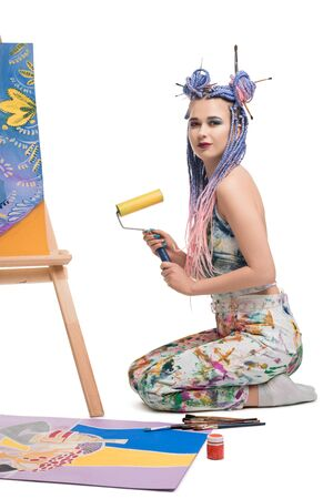 Sexy girl with brush sitting near easel view