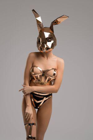 Slim girl in bdsm lingerie and mask shot Foto de archivo