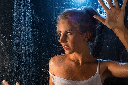 Girl in t-shirt having shower portrait in the dark