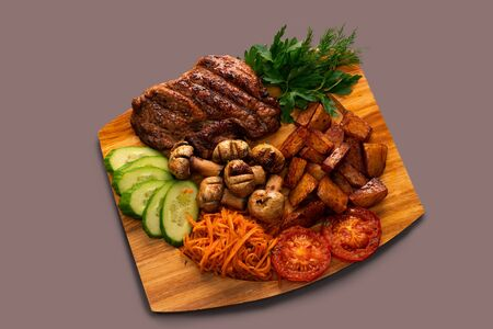 Fresh steak with tomatoes, cucumbers and salad on wooden cooking board high angle view