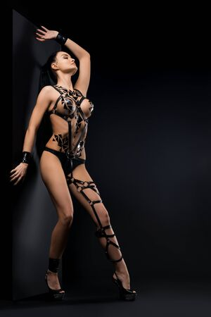 Sexy woman in black tape and bdsm wear near wall