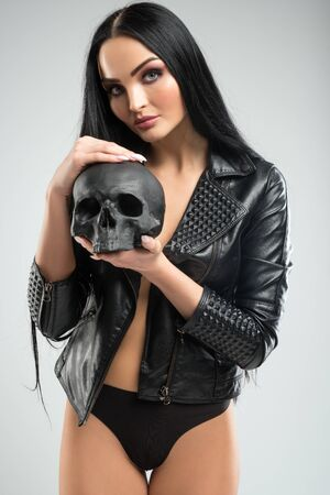 sexy brunette in leather jacket with black skull