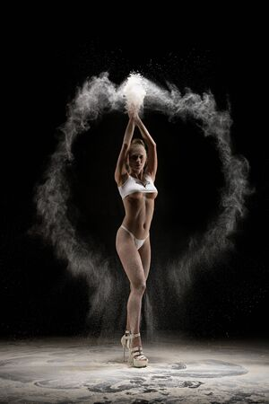 Sexy woman in underwear dancing with dust