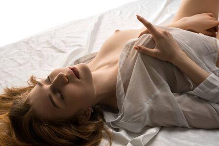 Sexy woman masturbating on bed at home