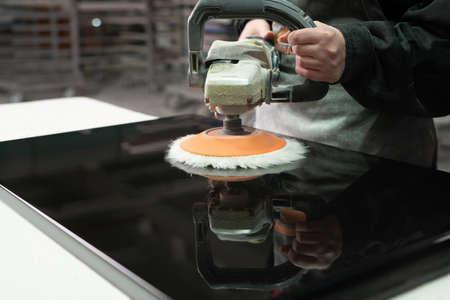 Polishing black wood panel with grinder machine