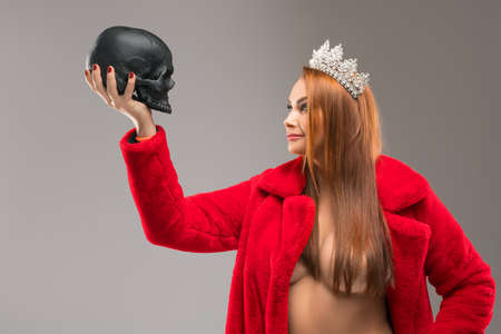 Sexy queen looking at black human skull