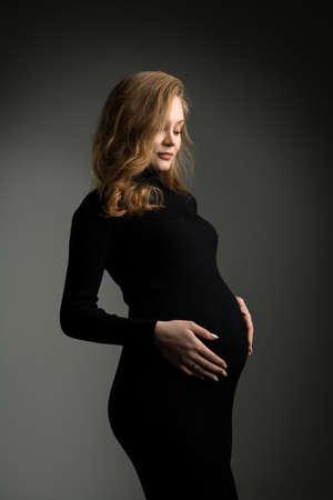 Pregnant woman in black dress in studio