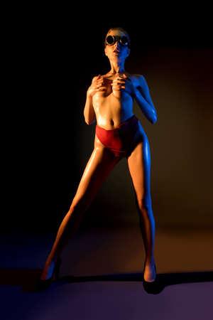 Sexy woman in futuristic goggles covering breast 版權商用圖片