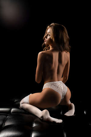 Sensual young female in sexy underwear with naked spine sittng on leather sofa
