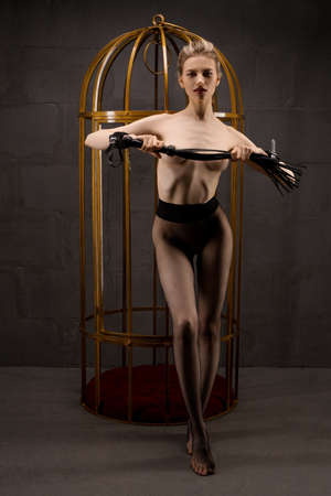 Sexy woman with whip standing near cage